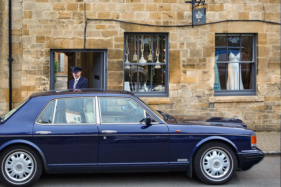 chauffeur helping guest out of Bentley Brooklands for wedding dress shop appointment in Chipping Campden