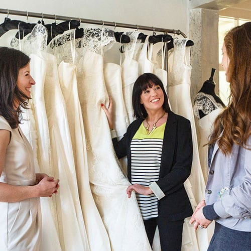 bride-to-be in dress shop with wedding planner