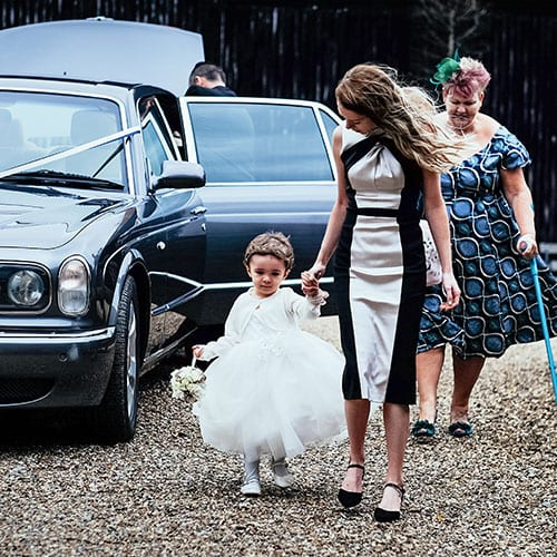 wedding guests and bridesmaids by wedding car
